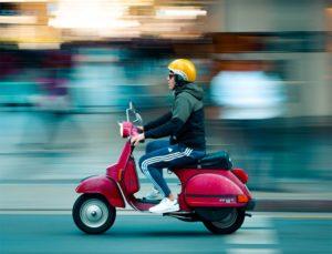 Bild von einem roten Moped und Fahrer mit gelben Helm
